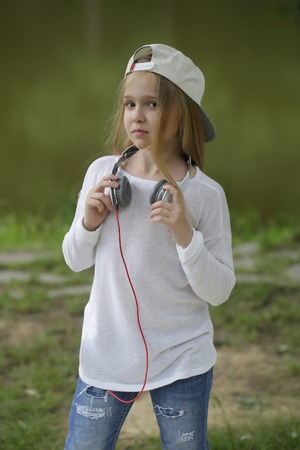 earpiece: small girl kid with long blonde hair and pretty smiling happy face in white hat with headphones on head standing outdoor near water on green natural background