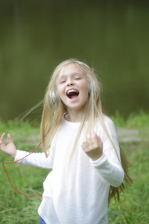 earpiece: small girl kid with long blonde hair and pretty smiling happy face in white with headphones on head standing outdoor near water on green natural background