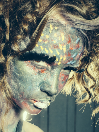 Woman with unusual paint make-up and curly hair in studio