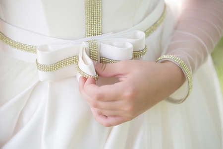 sequins: Beautiful belt with bow on white girl dress with bright golden sequins