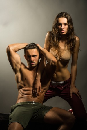 muscle guy: young sexy couple of pretty woman in beige bra with wet hair and handsome macho man with muscular torso and athletic body in studio on grey background Stock Photo
