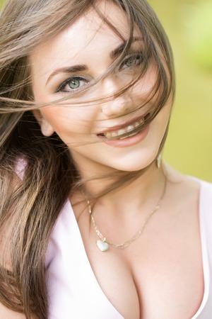 busty: mujer joven tetona con la cara hermosa y el pelo largo sonríe al aire libre en la naturaleza del verano