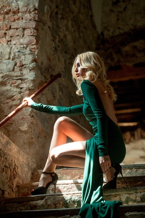 stone stairs: Young woman blonde dressed in fashion splendid green dress having sexy legs in black high-heeled shoes posing on old stone stairs indoor Stock Photo