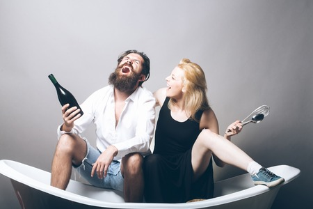 young family couple of blonde smiling pretty girl with kitchen utensils and bearded man with long beard holding wine bottle sitting on bathtub. household, everyday life and routine