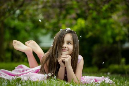 ragazze a piedi nudi: Bella bambina in abito rosa con i capelli lunghi bruna e sorridente viso disteso a piedi nudi sul prato verde in primavera petali di fiore in fiore all'aperto