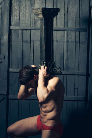 atlantes: Young man with muscular body holding hard column. Atlantes support, power.