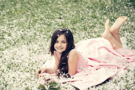 Beautiful little girl in pink dress with long brunette hair and smiling happy face lying barefoot on green grass covered with spring flower blossom petals outdoor