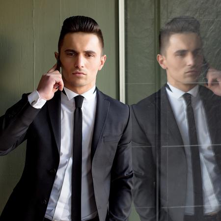 conversaciones: El hombre joven modelo sensual elegante hermoso en juego con la corbata flaca conversaciones de escudo abierto en el teléfono móvil mira la mano por delante en el bolsillo refleja en el espejo sobre fondo gris