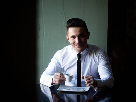 wears: Man young handsome elegant model wears white shirt black skinny necktie sits at table holds cup of coffee and smiles in camera indoor on grey background Stock Photo