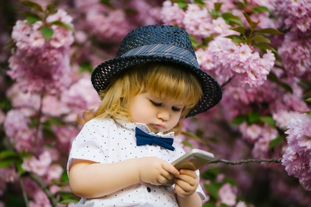 Small boy in white shirt and retro hat with bow tie with blonde hair playing on mobile phone in spring pink flower blossom Banque d'images