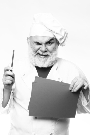 grimace: Bearded senior cook man with grimace face pointing recipe at the cookbook at the kitchen in hat, black and white Stock Photo
