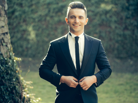 Man young handsome elegant model buttons suit coat with black skinny necktie smiles looks in camera poses on landscape on natural background