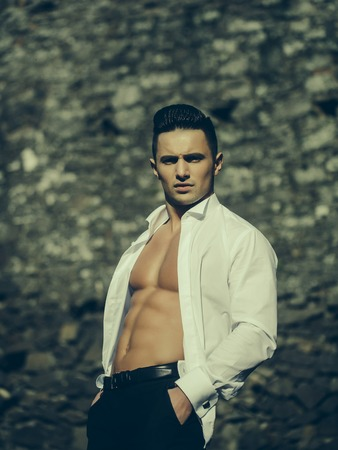 barechested: Man bare-chested young handsome sensual model in white shirt gaped open poses with hands in black trouser pockets outside on masonry background