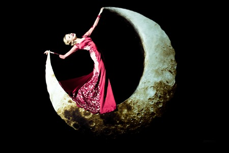 crescent: Beautiful young woman with blonde hair posing on crescent moon in long evening elegant dress red color on black background Stock Photo