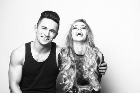 Young couple of muscular boy and girl smiling and sitting in studio, black and white