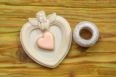 White angel photo frame with white bobbin of thread and decorative heart Stock Photo