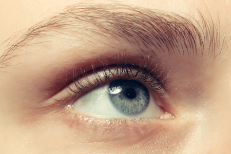 Close up of a blue beautiful eye. Attractive girl looks up 写真素材
