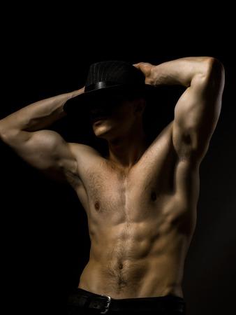nackte brust: Junger stattlicher Mann mit muskulösen Körper in Hut mit nackten Brust und Rumpf im Studio auf schwarzem Hintergrund aufwirft