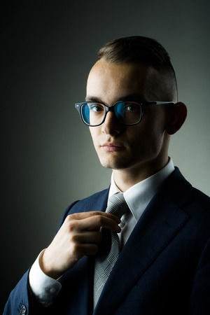 sociable: young fashion businessman with nerd glasses and stylish hairdo in jacket straightening tie posing on grey background Stock Photo