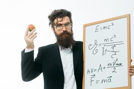 giovane bello scienziato barbuto o un professore in bicchieri con la barba lunga detenzione mela e bordo insegnante con formula e Newton la legge di Einstein isolato su sfondo bianco