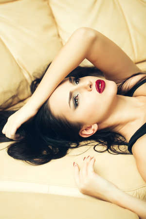 beige lips: Attractive girl with red lips on the beige couch