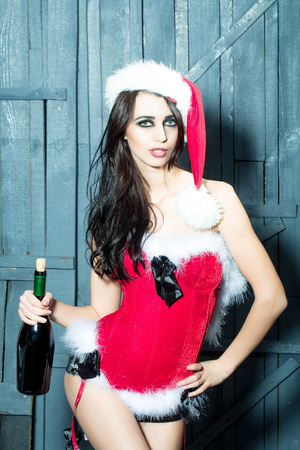 Attractive woman in Santa Claus corset and red hat in studio on wooden background with corked wine bottle Stock Photo