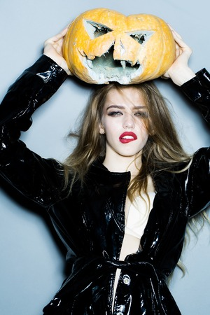 leather coat: Young sexy woman with bright glamour makeup on pretty face and beautiful hair in black leather coat holding scary halloween pumpkin on grey background