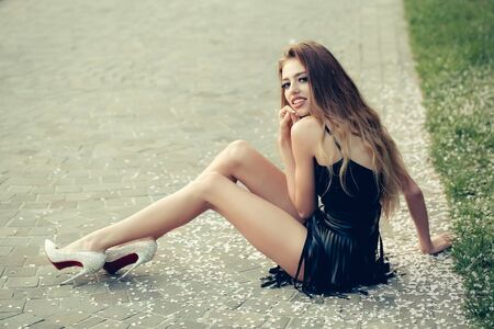 Young girl with beautiful face in glamour leather skirt and diamond shoes sitting on road Stock Photo