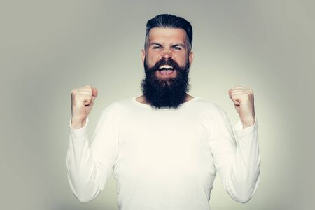 long beard: handsome young man with long beard and moustache on happy face with yes gesture of punches on grey background in studio