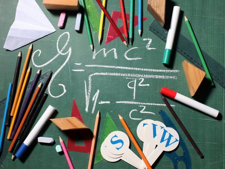 quadratic: Mathematic quadratic root formula drawing on green blackboard with chalk surrounded by school stationery alphabet markers colored pencils paper plane rules Stock Photo