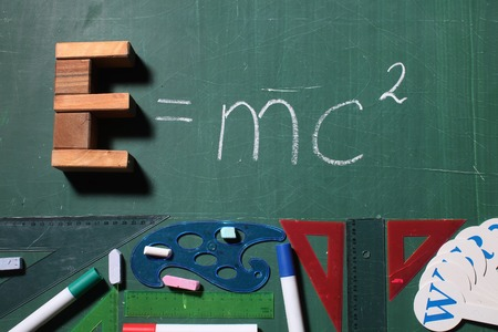 mc2: Theory of relativity physics formula made of wooden cubes and drawing by chalk on school green blackboard above colored markers colorful curve rules triangles alphabet Stock Photo