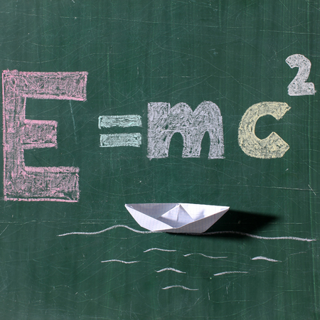 mc2: Theory of relativity formula text word drawing by colorful chalks and white boat paper origami on sea waves on school green chalkboard