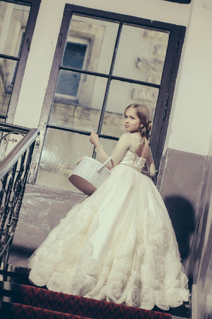 prom queen: small girl kid with long blonde hair and pretty face in prom princess white dress with basket standing near building glass big window on stairs
