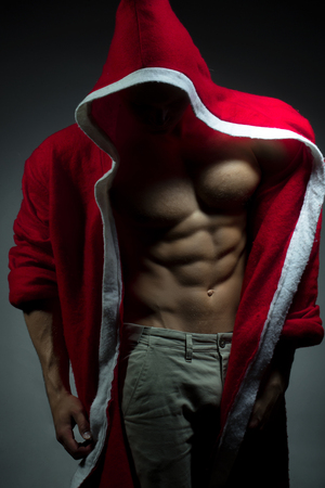 muscular body: sexual young new year man with muscular body in red christmas santa coat posing on studio background Stock Photo