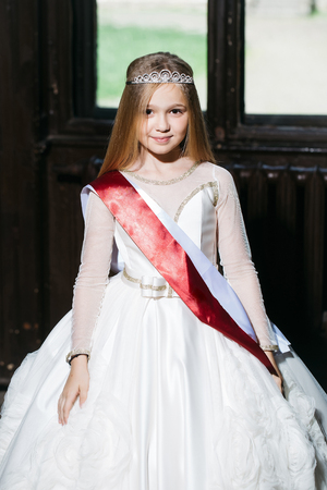 prom queen: small girl kid with long blonde hair and pretty happy smiling face in prom princess white dress and red miss ribbon with crown on head