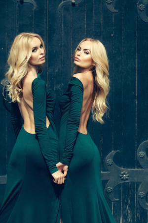 young pretty women with long lush curly blonde hair and sexy bodies in green dresses standing near iron big door