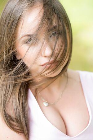 tetona: mujer joven con la cara hermosa tetona y el pelo largo presenta al aire libre en la naturaleza del verano Foto de archivo