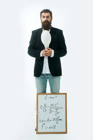 giovane bello scienziato barbuto o un professore con la barba lunga che tiene scheda insegnante con formula e Newton la legge di Einstein isolato su sfondo bianco