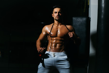 saltar la cuerda: Handsome young man with sexy muscular wet body bare torso and chest holding jump rope