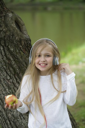 small girl kid with long blonde hair and pretty smiling happy face in white with headphones on head eating apple standing outdoor near water on green natural background