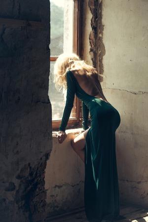 벌거 벗은 다시 녹색 실내 섹시 한 드레스를 입은 금발 머리를 가진 젊은 여자 실내 오래 된 창 근처 포즈