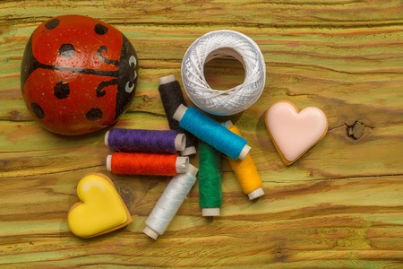 Colorful bobbins of thread with ladybug and decorative hearts Stock Photo