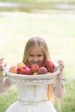 prom queen: small girl kid with long blonde hair and pretty smiling happy face in prom princess white dress standing sunny day outdoor near water with fruit basket of red apples peach and cherry Stock Photo