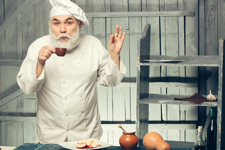 man nuts: Bearded man cook in chef hat with apple nuts pumpkin and honey drinking coffee on wooden background