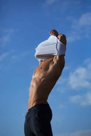 undressing: young macho man model athlete with muscular sexy body and wet bare chest outdoor on sky background undressing white shirt