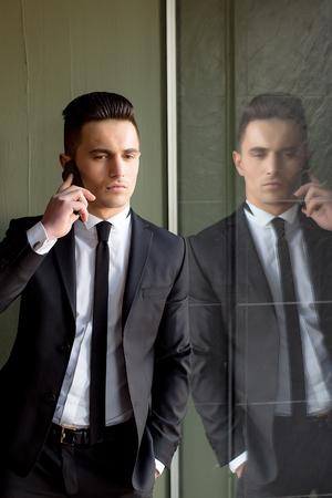 conversaciones: El hombre joven modelo sensual elegante hermoso en juego con la corbata flaca conversaciones de escudo abierto en el teléfono móvil mira hacia abajo mano en el bolsillo refleja en el espejo sobre fondo gris Foto de archivo