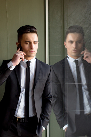 talks: Man young handsome sensual elegant model in suit with skinny necktie open coat talks on mobile phone looks down hand in pocket reflects in mirror on grey background