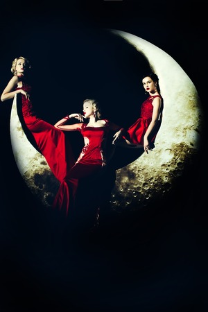 Beautiful young women with blonde and brunette hair posing on crescent moon in long evening elegant dress red color on black background