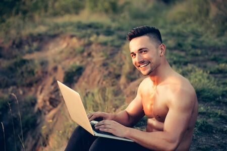 nackte brust: Young handsome smiling man with muscular sexy body and bare chest sitting with laptop outdoor sunny day
