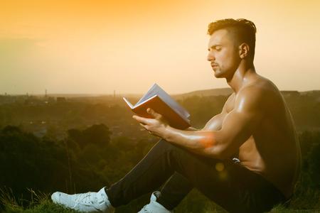 nackte brust: Junger stattlicher Mann mit dem muskulösen sexy Körper und nackte Brust mit Buch im Freien sonnigen Tag sitzt